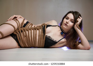 Young woman in black lingerie bound with a rope in Japanese technique shibari.  Office violence concept