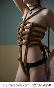 Young woman in black lingerie bound with a rope in Japanese technique shibari. Violence concept