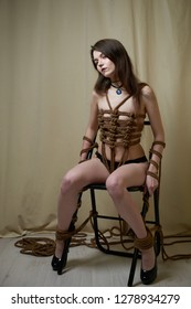 Young woman in black lingerie bound with a rope in Japanese technique shibari. Home violence concept