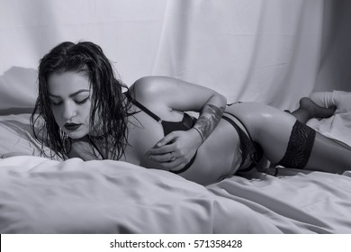 Young woman with black lingerie posing on bed, B&W