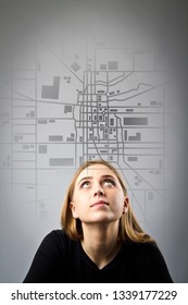 Young woman in black is looking for a route on the city map. Girl and the city map.