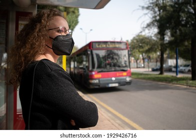 Young woman with black mask waiting for the bus in the city. Prevention of covid 19 or coronavirus in public transport.