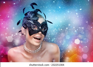 Young woman with black masquerade mask with feathers, fantasy background