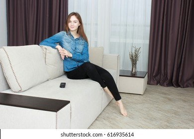 Young woman In black pants and a blue shirt watching TV
