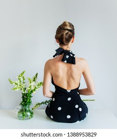 Young woman in black polka dot dress sitting on a table near Matthiola flowers