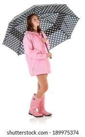 Young woman with black polka dot umbrella and pink rain coat and boots. Studio shot, on white background with reflection.