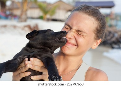 young woman with black puppy in the hands