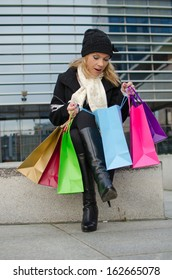 Young woman in black with shopping bags
