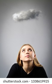 Young woman in black and small cloud. Imagination and virtual cloud concept.