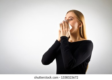 Young woman in black is sneezing. Sneeze and allergy concept.
