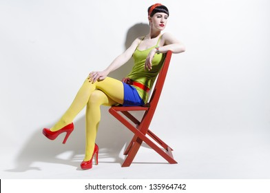Young woman with black straight hair wearing colorful clothes remixed and sitting on a red chair in front of a white background.