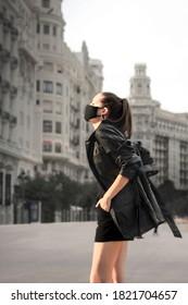 Joven con estilo negro y máscara negra disfrutando del sol en medio de la ciudad europea. Hora de oro y coronavirus. Centro urbano vacío y modelo posando con máscara y sol