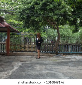 young woman with black suit shirt and black skirt relaxation in her home with large space concrete floor and big trees