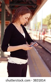 A young woman in black sweater holds a cell phone and checks her watch at the train station.