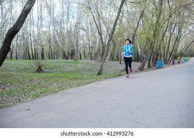 Young woman in black tights running around the Park holding a bottle of water