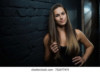 Young woman in black top leaning against black brick wall. Copyspace.