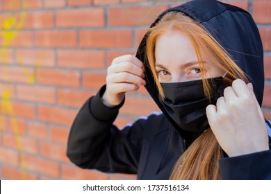A young woman in a black tracksuit puts a hood on her head. A girl with a black mask on her face against the coronavirus disease COVID-19.