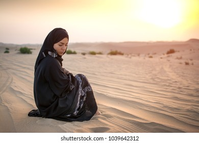 Young woman in black traditional clothes sitting on sand against sunset over desert.