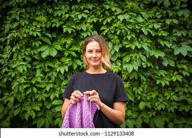 A young woman in a black T-shirt and jeans shorts stands knitting needles and an untied sweater made from natural lilac wool threads against the background of a green wall of grapes