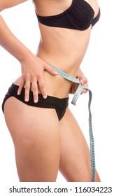 Young woman in black underwear measuring her waist
