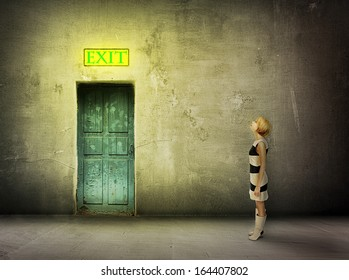 young woman in black and white dress stand in front of blue door in dark grungy room watch on glowing exit sign - find the way out