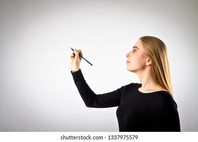 Young woman in black is writing something.