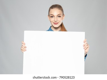 Young woman with blank advertising board on grey background