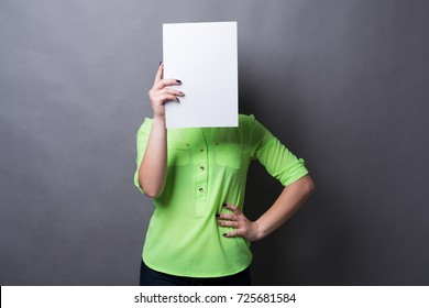 Young woman with blank white paper at face. Serious girl covering her head with advertising sheet, copy space
