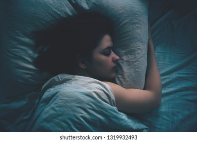 Young woman with blanket sleeping at night in bed top view.