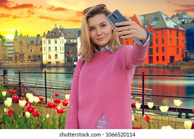 young woman blogger doing selfie on the background of the  Aalesund. beautiful places in Europe.
