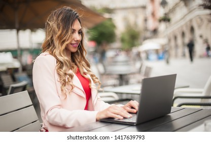 Young woman blogger freelancer in outdoor cafe with computer laptop, city street background