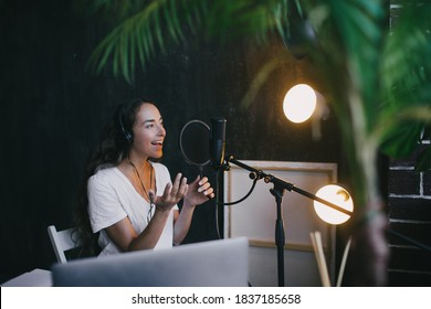 Young woman blogger with long black hair recording online podcast using her laptop, headphones and professional microphone in a studio.