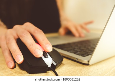 young woman blogger working at laptop at home close-up of hand on mouse