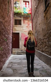 Young woman with blonde dreadlocks explores old portugese town.