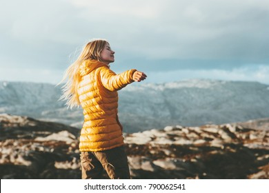 Young Woman blonde enjoying mountains landscape Travel Lifestyle happy emotions concept adventure outdoor active vacations in Norway girl tourist walking wearing yellow down jacket