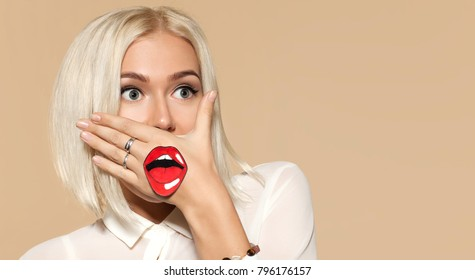 Young woman with blonde hair and painted red lips on her hand. Portrait of fashionable female person on beige background. Emotion of surprise and fright. Concept of tomfoolery and fun.