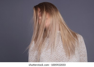 Young Woman With Blonde Long Hair Dancing on Gray Background