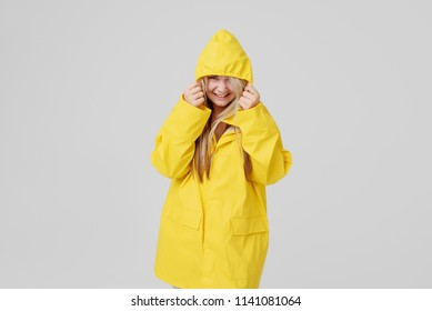 Young woman blonde in a yellow raincoat, with a hood on a head background hides from a rain on a grey background