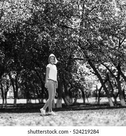 Young woman in blooming spring garden.