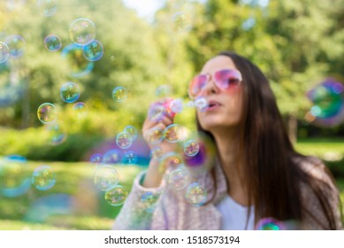 Young woman  blowing bubble in the park