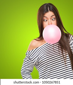 Young Woman Blowing Bubblegum and crossing her eyes against a green background