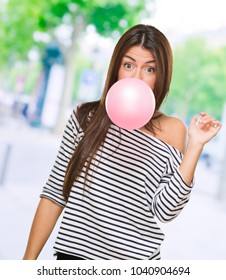 Young Woman Blowing Bubblegum, outdoor