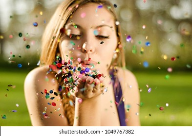 young woman blowing colorful glitter confetti outdoors