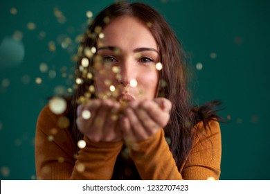 young woman blowing confetti from hands, gold glittery sparkly glamourous colour combination
