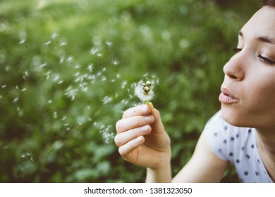Young woman blowing dandelion in  park spring summer background