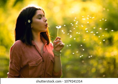Young woman blowing dandelion in the warm summer sunset. Spring allergy concept