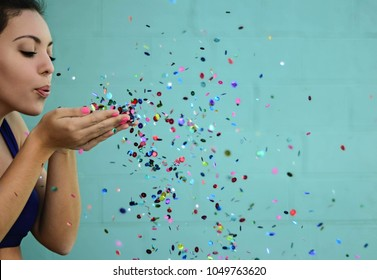 young woman blowing glitter in sports bra on blue background