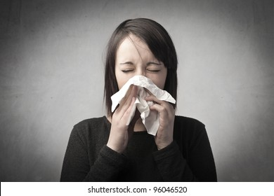 Young woman blowing her nose