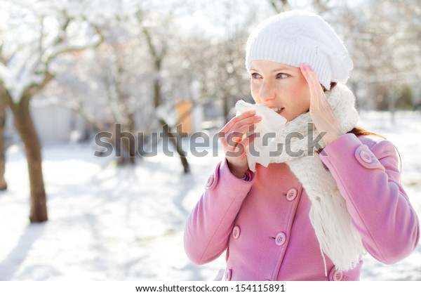 Young woman blowing her nose into a tissue in winter