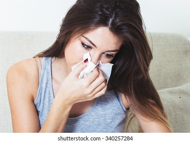 Young woman blowing nose in bed ill with temperature